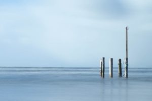 Nordsee umfließt Pfähle in der Nordsee vor Nebel