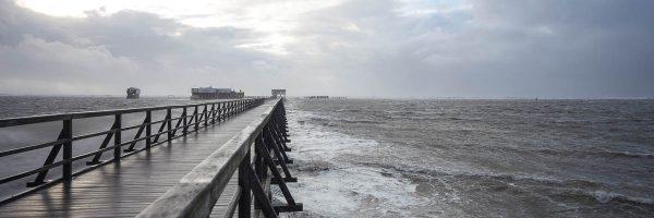 Seebrücke im Sturm mit Blick auf die Arche Noah